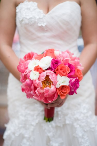 Coral charm peonies, white lisianthus, Amsterdam and pink lady roses make a perfect round bouquet.