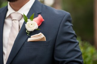 Classic boutonniere of white ranunculus, pink lady rose and Italian ruscus on a classic navy suit.