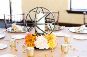 Black iron sphere with fall colored mums and peach carnations, gold crystals and votives to complete the look