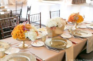 Set of three arrangements of fall colored mums, hydrangea, roses and maple leaves. Table set in all gold.