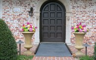 Front of Casa Feliz with large urns with bright colored floral