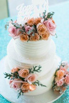 A beautifully decorated cake filled with Coral Spray Roses, Blush Standard Roses, and Dusty Miller.