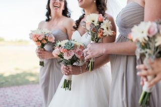 The pastel colors of the floral in the bridal and maids' bouquets pair perfectly with the neutral tones in their gowns.