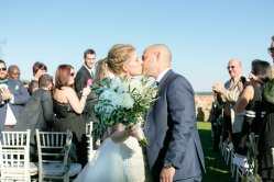 Our Bride and Groom sharing their first kiss as husband and wife as she displays her gorgeous loose and airy bridal bouquet, filled with Olive Branches, White Ranunculus, White Garden Roses, and White Peonies.