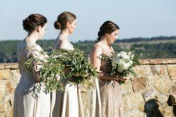 A shot of our Maids' during ceremony carrying their loose and airy textured bouquets filled with Olive Branches and Euchs.