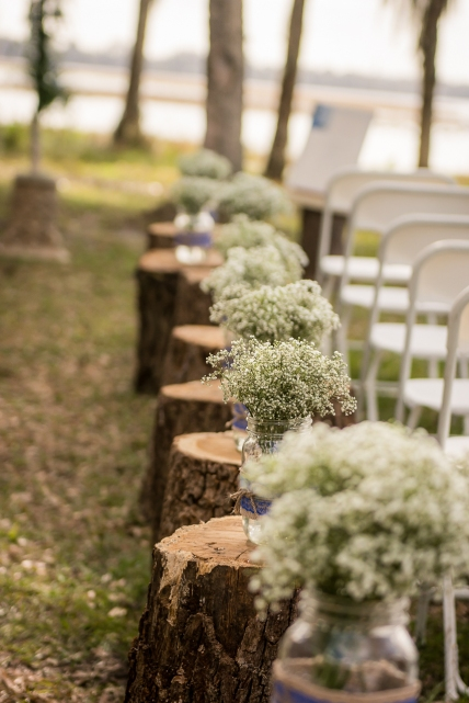 Ceremony setup with Babies Breath filled mason jars on stumps.