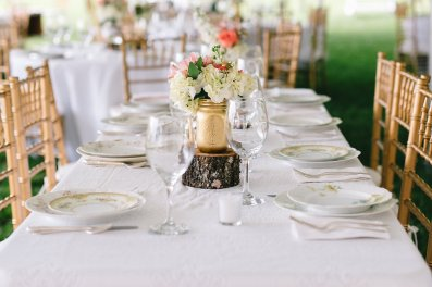 Guest table centerpieces inside gold mason jars filled with white hydrangea, white wax, coral roses, blush alstroemeria, and white stock, on top of log slices with antlers to accent.