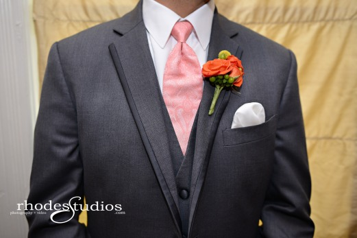 Grooms boutonniere of green jade hypericum, craspedia, and orange babe spray roses.