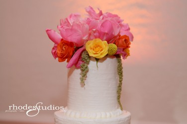 Cake floral of coral charm peonies, craspedia, golden galaxy spray roses, orange babe spray roses, and green amaranthus.