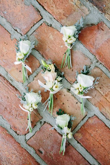 The boutonnieres were a modern design with stems showing and tied off with an ivory ribbon.