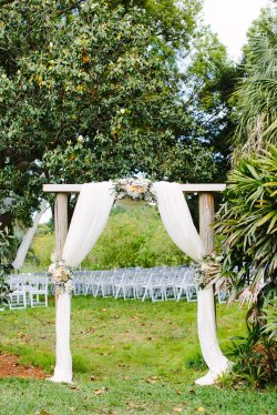 Entry Arch with ivory drape and gorgeous floral sides and center