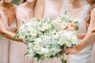 Cluster of bouquets in ivory garden roses, Juliet garden roses, white stock and eucalyptus.