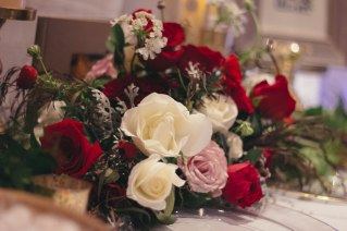 Our table scape at the wedding expo with a garland and center piece of red freedom roses, white tibet roses, ester roses, and dusty miller.