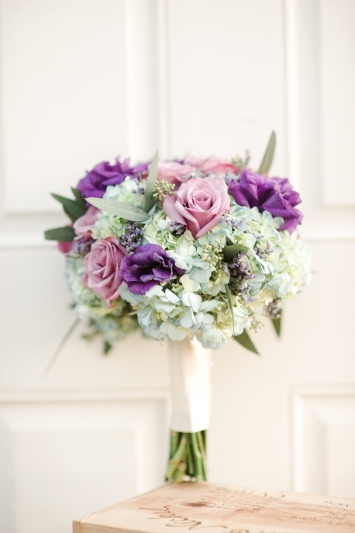 Bridal bouquet in blue hydrangea, lavender roses, purple lisianthks and seeded eucalyptus.
