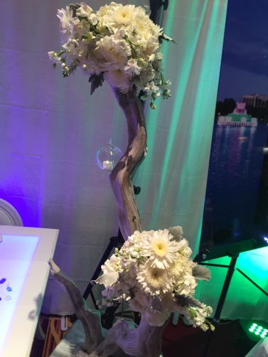 White hydrangea, white football mums, dusty miller, white tibet roses, and white stock on driftwood with starfish, seashells and sea glass.