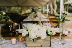 Rustic wood boxes with bud vases and votives flowed down the all of the family style tables.