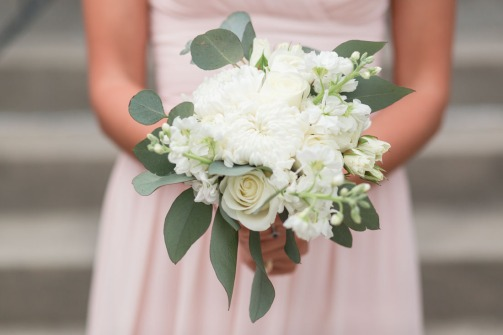 Bridesmaids bouquet using white football mums, white ranunculus, white stock, white tibet roses, silver dollar eucalyptus, and white majolika spray roses.