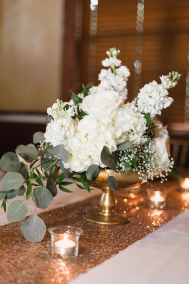 This center piece was created in a gold footed wooden bowl using white hydrangea, white stock, babies breath, white tibet roses, white majolika spray roses, ruscus, and silver dollar eucalyptus.
