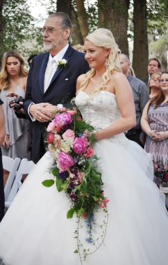 Our beautiful bride with her cascading bouquet filled with ivy, mini sunflowers, pink snapdragons, bright pink peonies, bright blue delphinium, queens ann, dark purple lisianthus,bubble gum pink spray, italian ruscus, thistle, and pink garden roses.