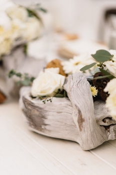 Driftwood centerpieces with roses, mums, hydrangea, succulents and eucalyptus.