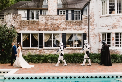Bride and groom being escorted away by Darth Vader and two storm troupers.