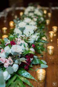 Garden, spray and standard roses with lush greens to create garlands going down the table.