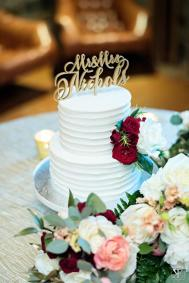 Sweet buttercream cake with small details of floral and a laser cut cake topper.