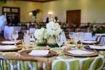 Gold mercury vases with tropical greens and hydrangea.