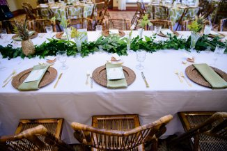 Garlands with small eclectic vases with interesting floral in each vase.