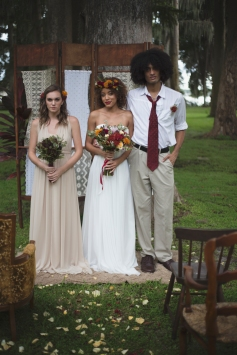 Grooms boutonniere of burgundy and yellow mums with greens and hypericum berries. Brides flower halo made of yellow and burgundy mums and bouquet created with yellow and burgundy mums, purple snap dragons, hypericum berries, proteas, ivory standard roses, and greens.