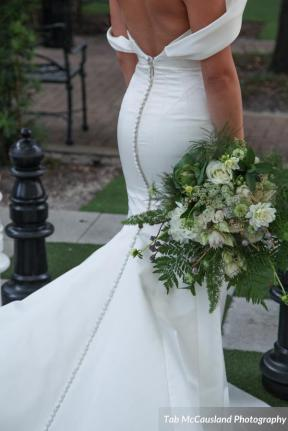 Bridal bouquet created with a mix of greens, cabbage, wax flower, nigella, white tibet roses, queens anne lace, blushing bride, and white dahlias.