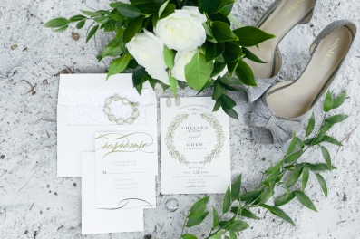 Elegant shot of the wedding stationary with the brides shoes and bouquet