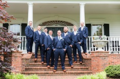 groomsmen in navy with ivory and mauve boutonnieres