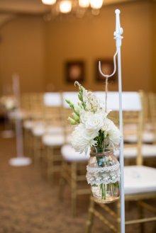 white aisle decor on shepherds hook with spray roses and lisianthus