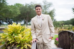 dapper groom in rustic chic kaki tux with blush flower boutonniere