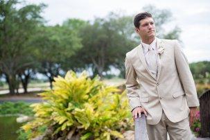 romantic wedding groom in kaki tux with blush flower boutonniere